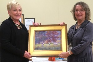 Sue Beans (L) won the raffle of featured artist Helena van Emmerick-Finn's painting Sheep in Autumn Photo by Audrey Chen